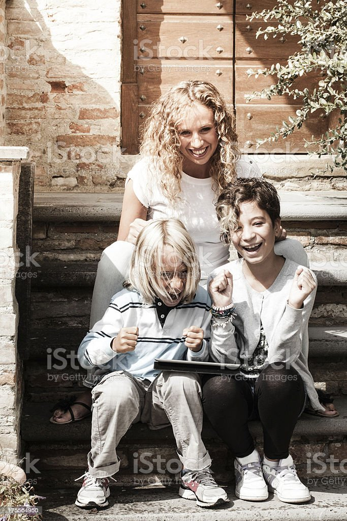 Young Woman and Children Using Tablet PC royalty-free stock photo