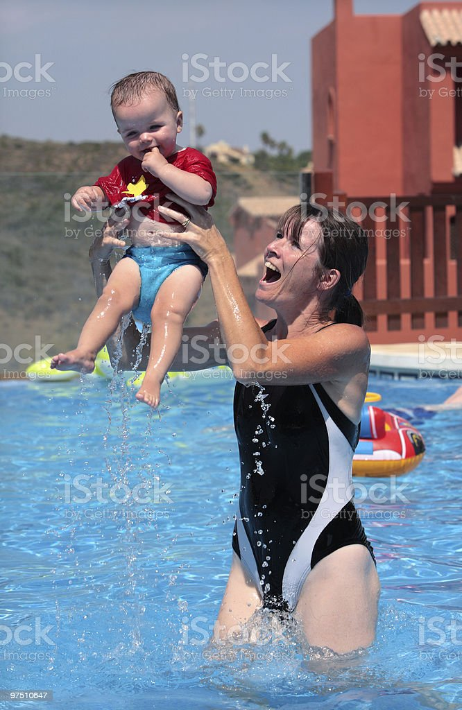 Young woman and daughter playing in the swimming pool royalty-free stock photo