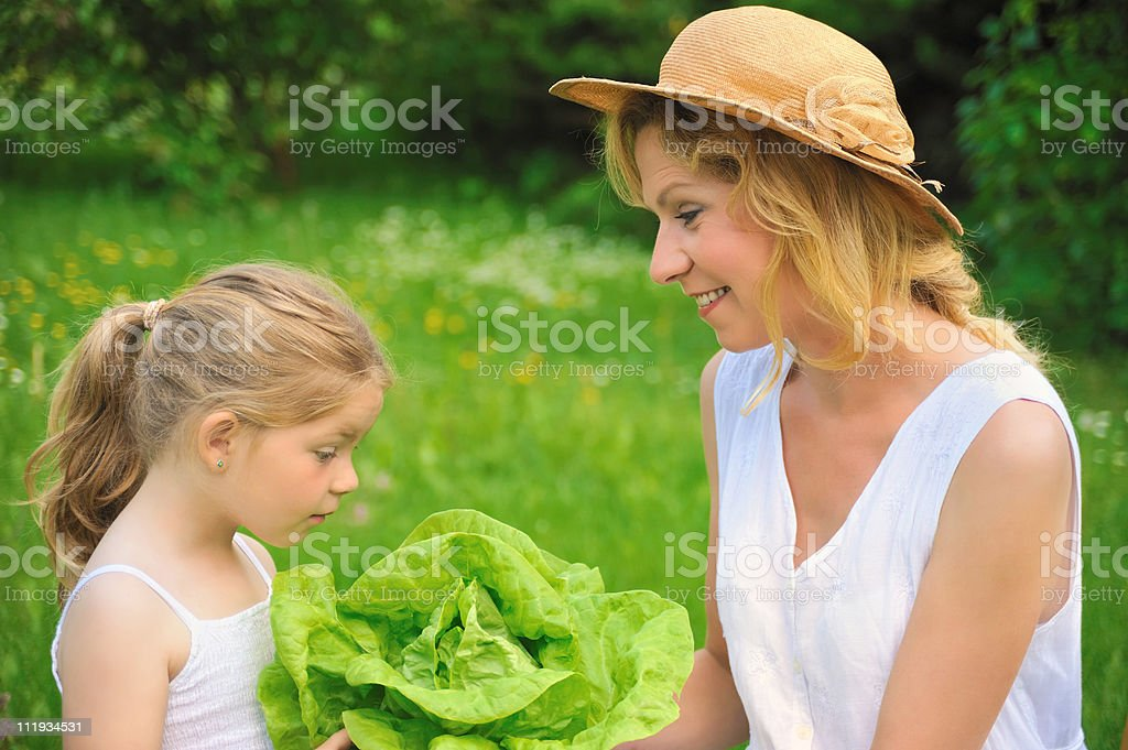 Young woman and daughter  with fresh lettuce royalty-free stock photo