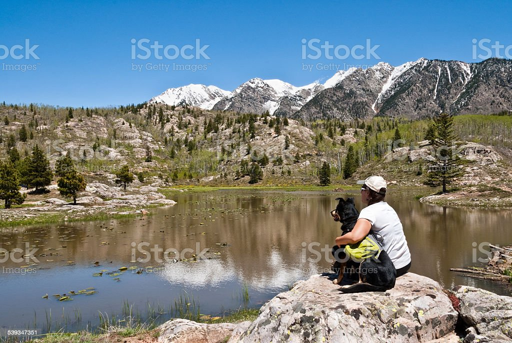 Young Woman and Dog Sitting by a Beaver Pond stock photo