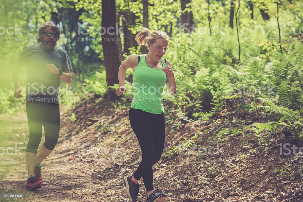 Young woman and elderly man running in the forest stock photo