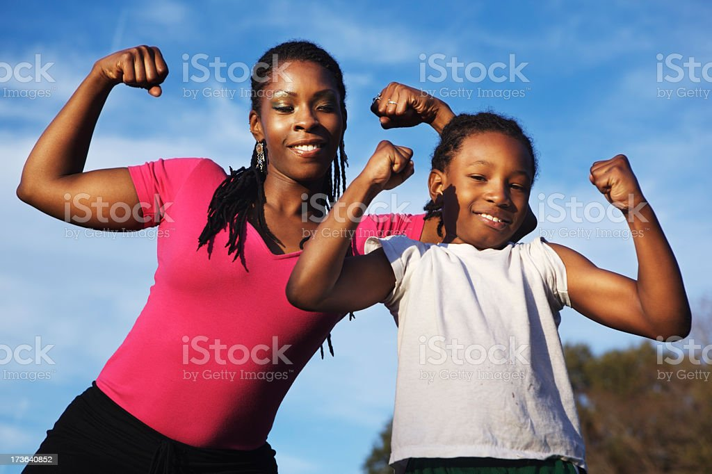 Young woman and girls showing of their muscles royalty-free stock photo