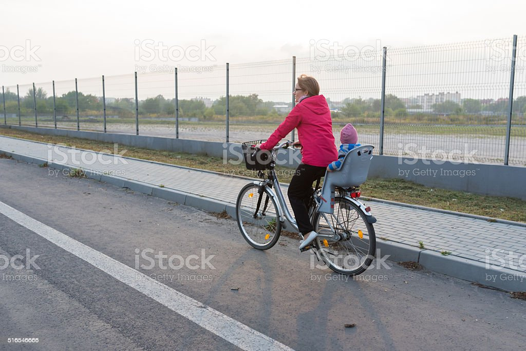 Young woman and her baby riding a bicycle stock photo