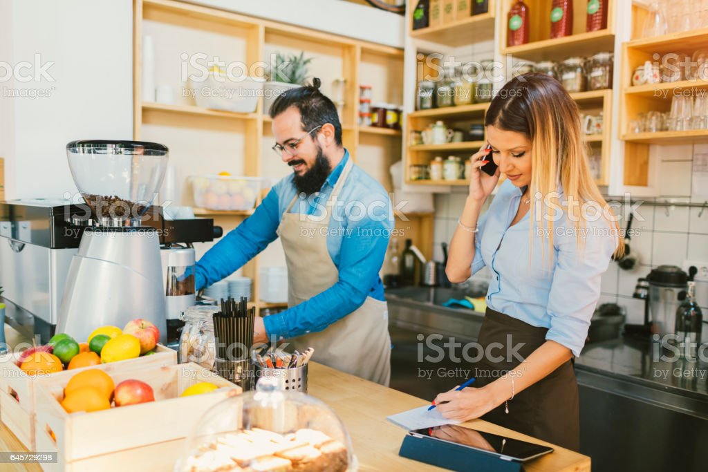 Young Woman And Her Colleague Working In Cafe stock photo