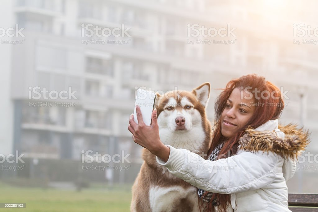 Young woman and her dog doing selfie stock photo