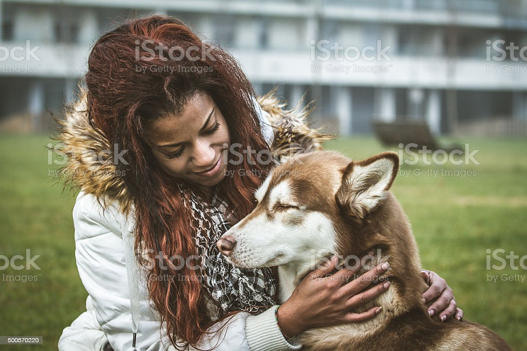Young woman and her dog in urban park stock photo