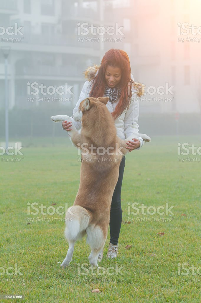 Young woman and her dog running and playing stock photo