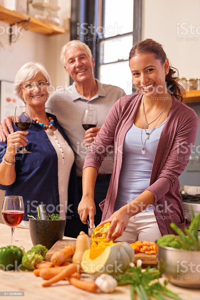 Young woman and her grandparents cooking together in the kitchen stock photo