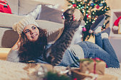Young woman and her kitten on Christmas Eve