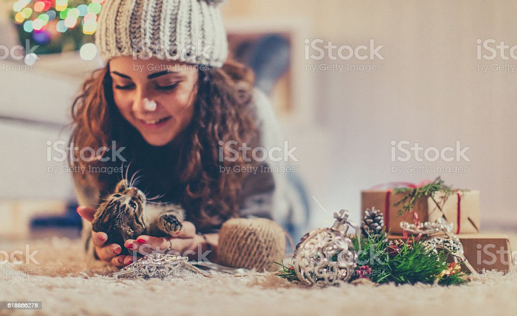 Young woman and her kitten on Christmas Eve stock photo