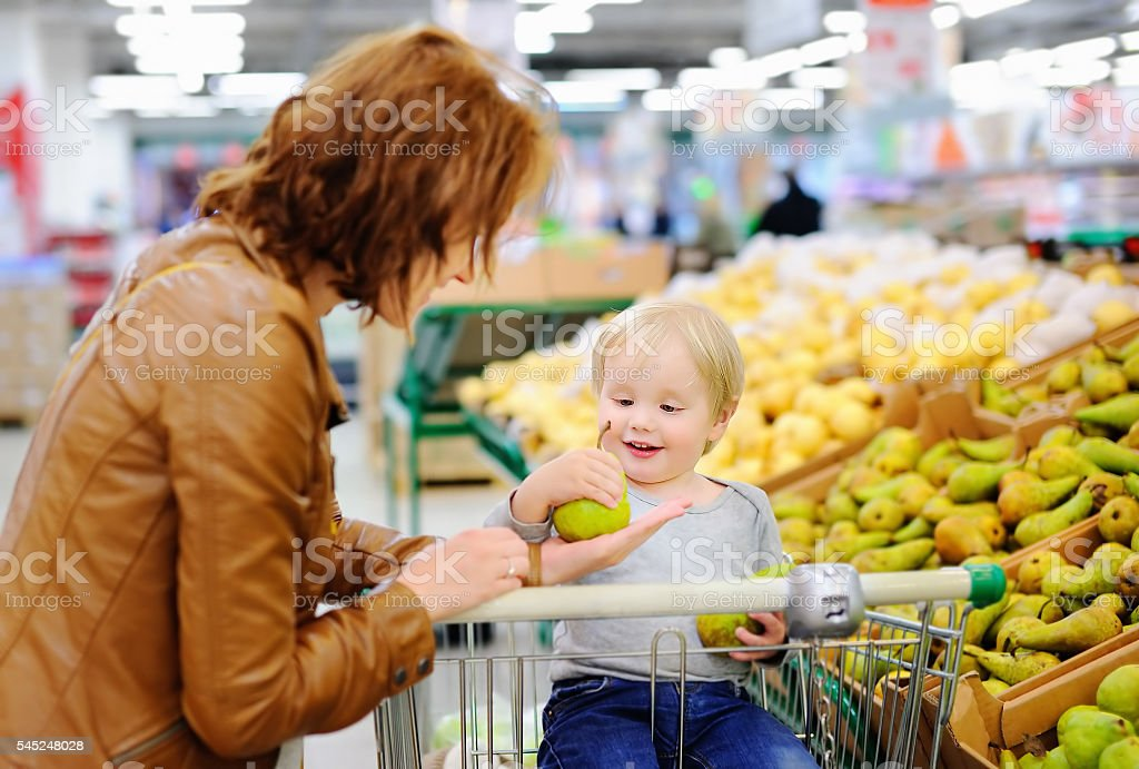 Young woman and her toddler son in a supermarket stock photo