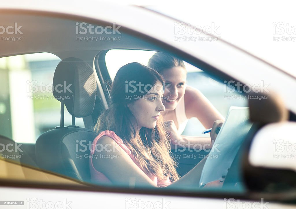 Young woman and instructor by the car stock photo