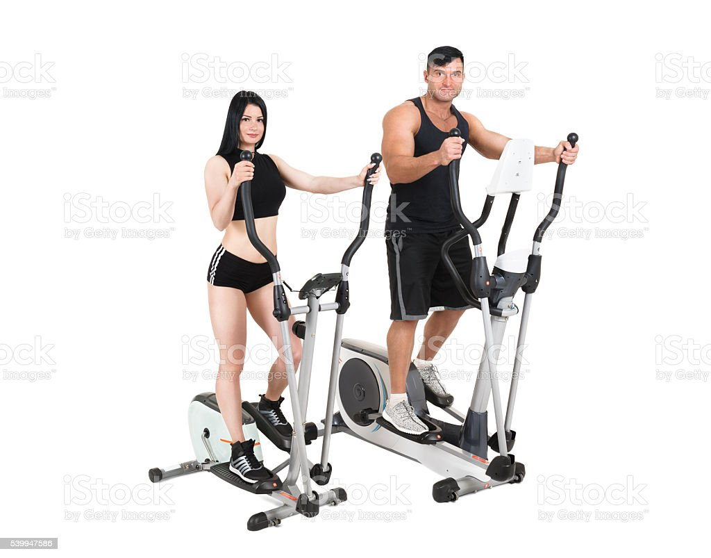 young woman and man doing exercises on elliptical cross trainer stock photo