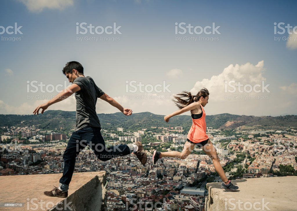 Young woman and man jumping and  practicing parkour stock photo