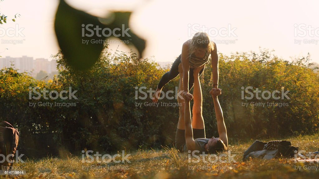 Young woman and man practicing acrobatic yoga in the autumn stock photo