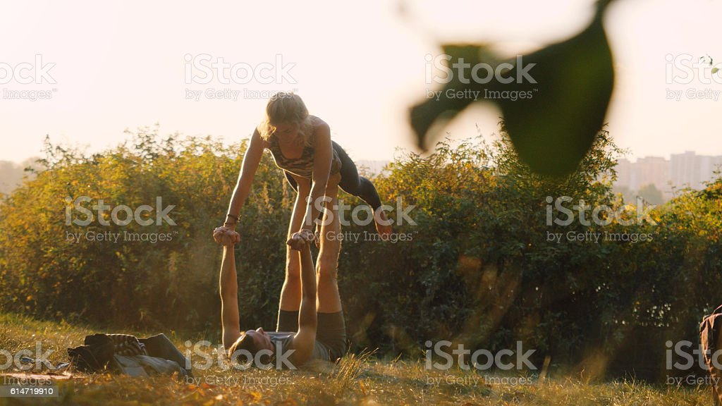 Young woman and man practicing acrobatic yoga in the park stock photo