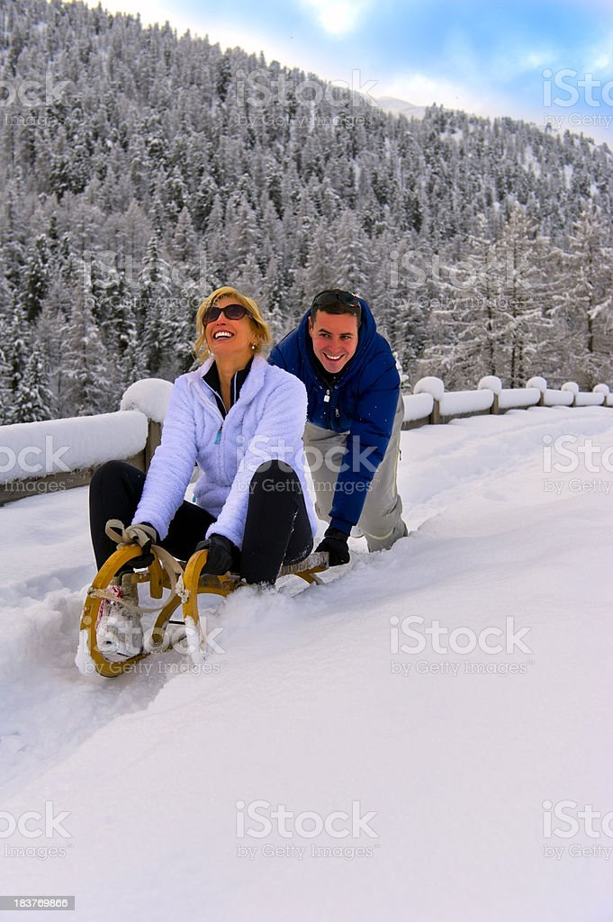 Young woman and man sledding at the snow royalty-free stock photo