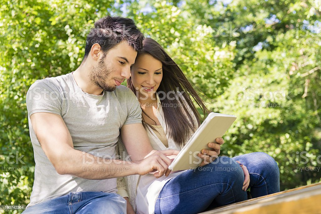 Young woman and man smiling using digital tablet royalty-free stock photo
