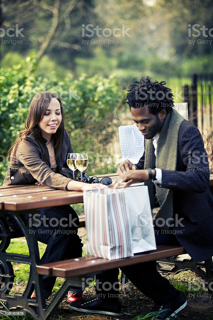 A young woman and man taking a shopping break at the park royalty-free stock photo