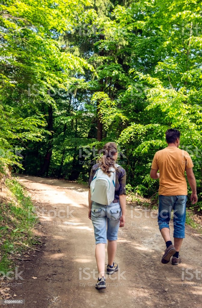 Young woman and man walking in the forest in summer stock photo