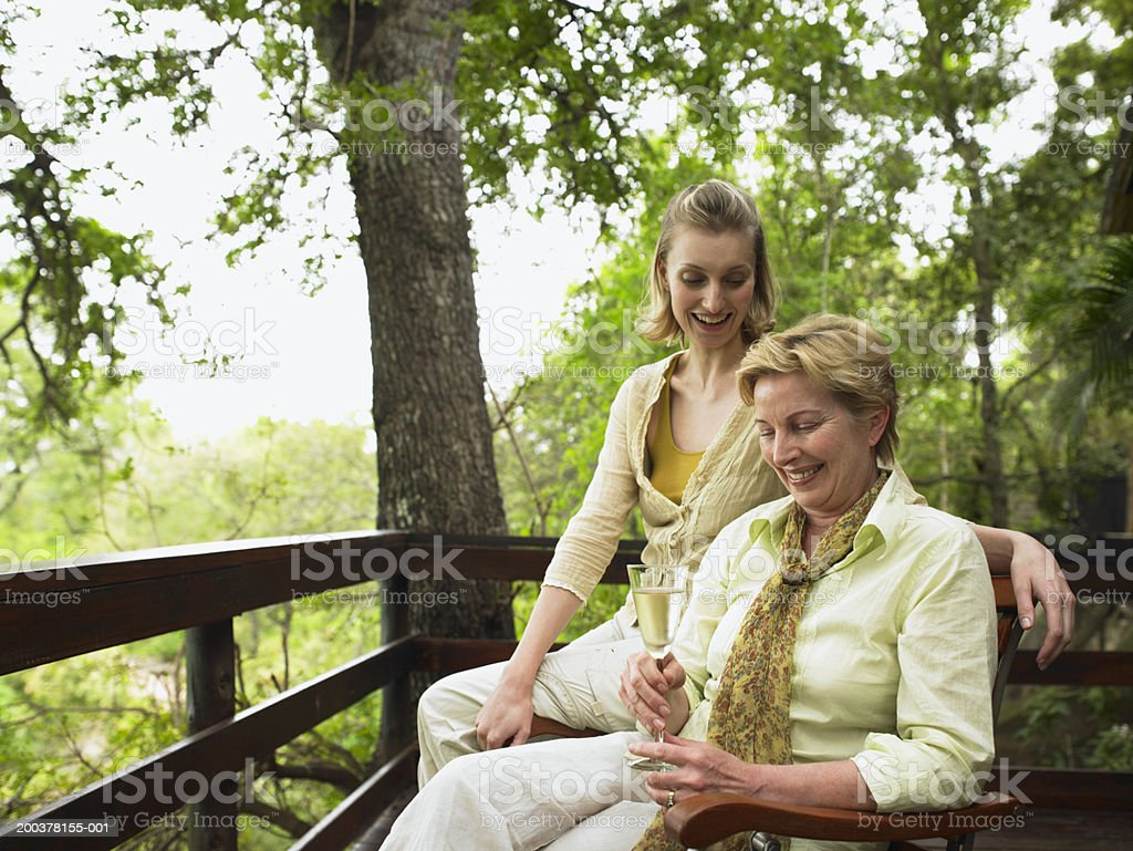 Young woman and mature woman holding drink, on balcony, smiling royalty-free stock photo