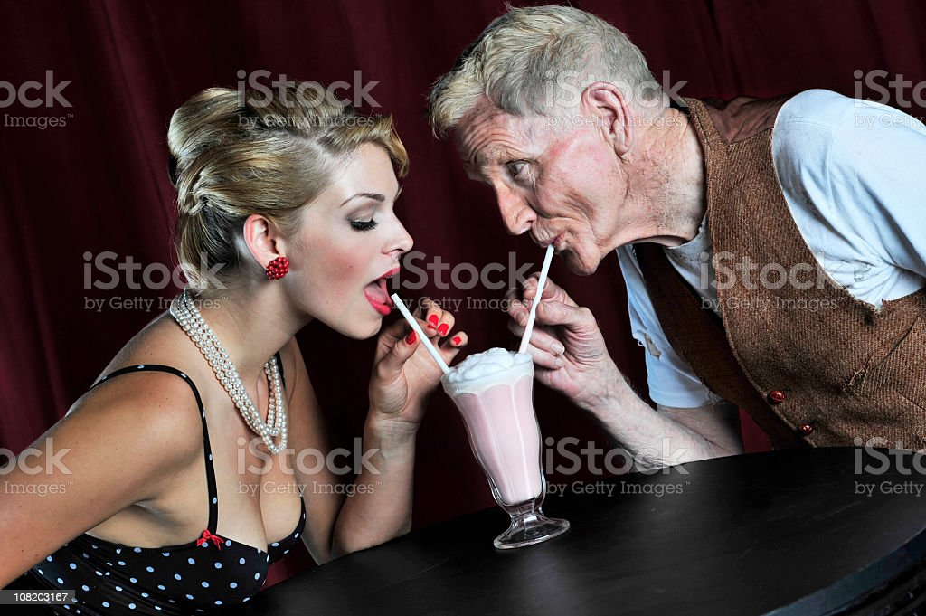 Young woman and older man sharing a milkshake stock photo