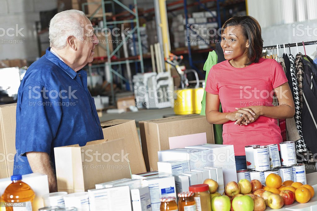 Young woman and older man working at food donation center royalty-free stock photo