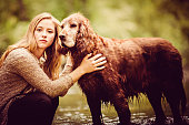 Young Woman And Pet Dog Outdoors In Nature
