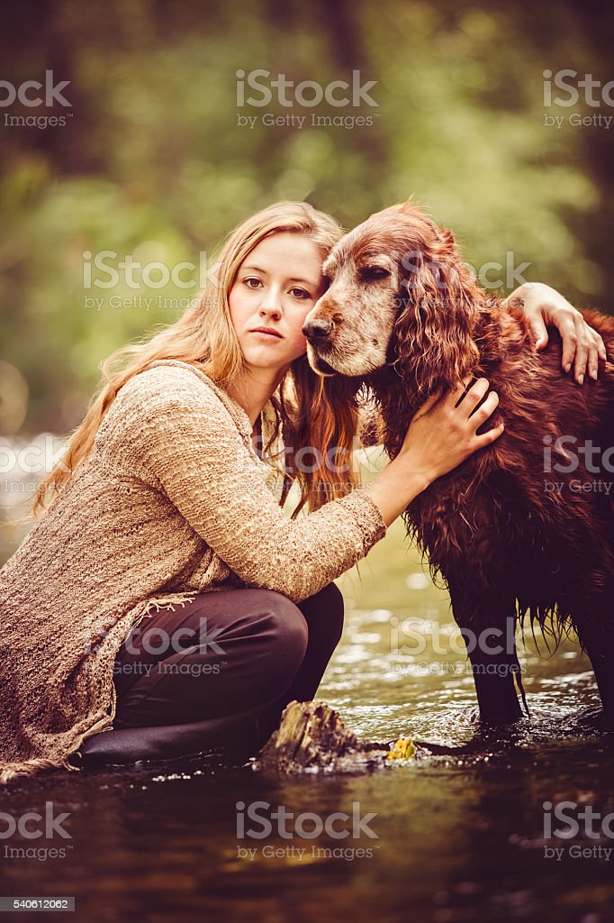 Young Woman And Pet Dog Outdoors In Nature stock photo
