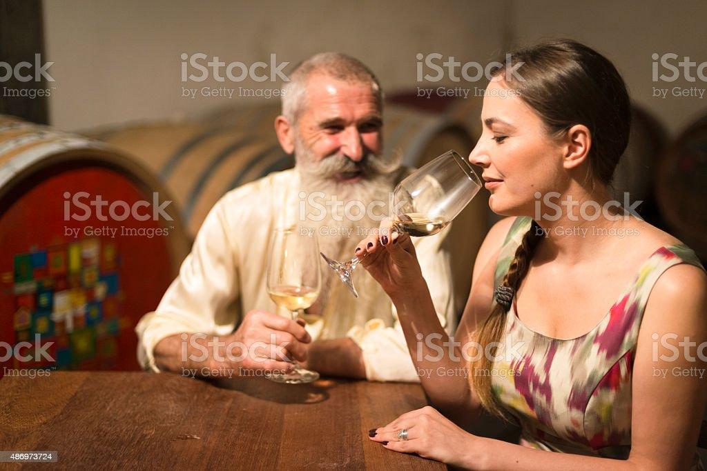 Young Woman and Senior Man Tasting White Wine, Cellar, Europe stock photo