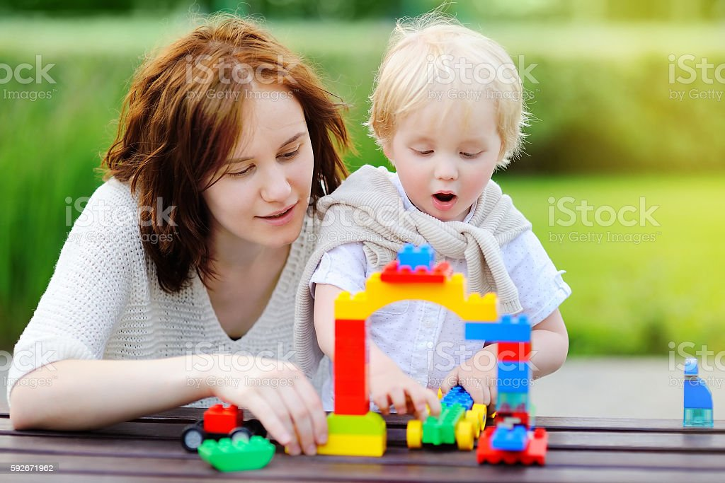 Young woman and  toddler son playing with plastic blocks stock photo