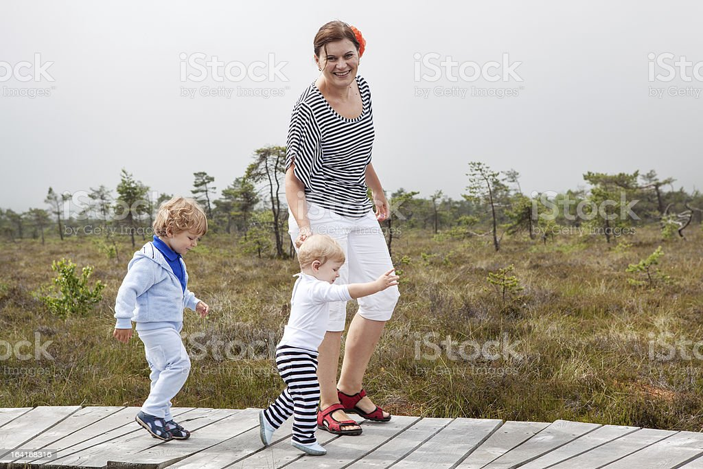 Young woman and two little toddler boys in nature park royalty-free stock photo