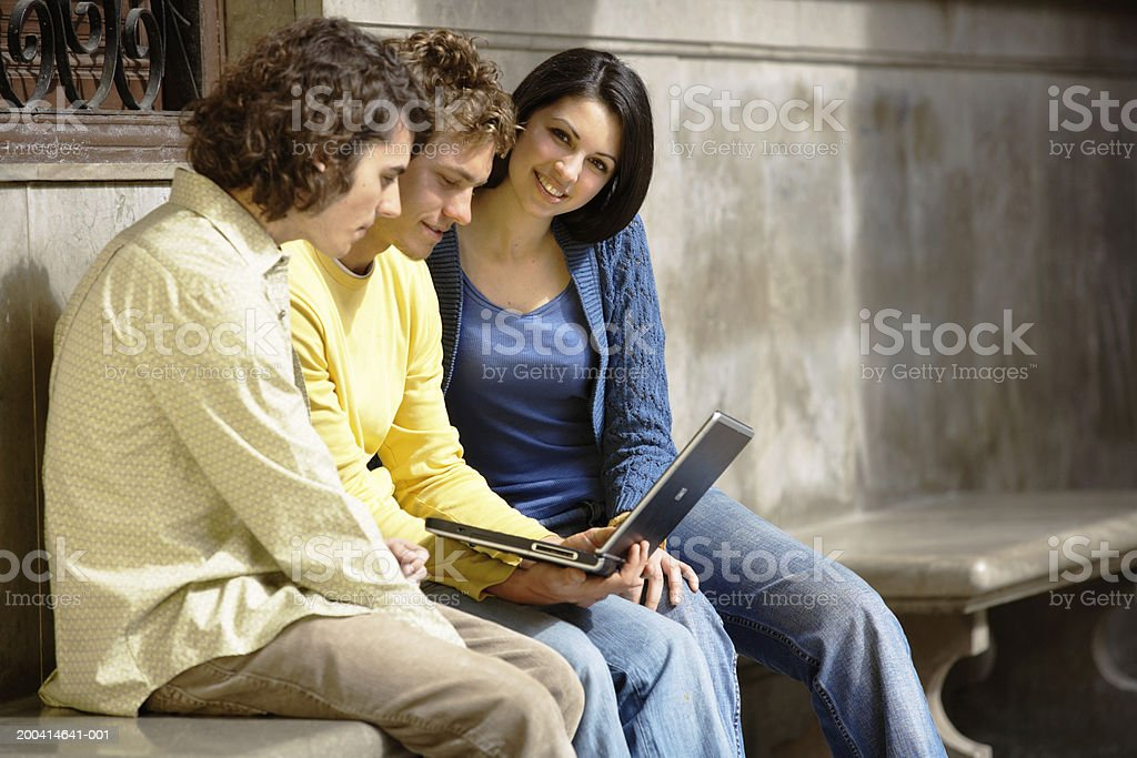 Young woman and two young men sitting on bench using laptop, smiling royalty-free stock photo