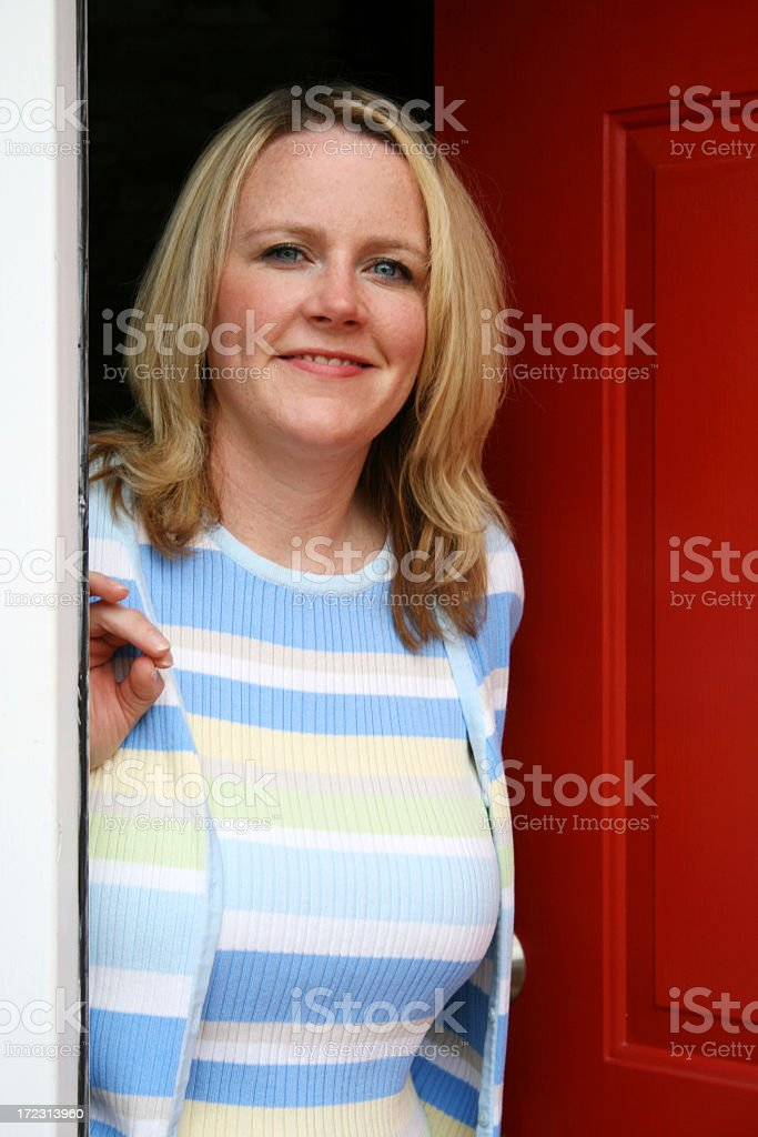 A young woman answering the door stock photo