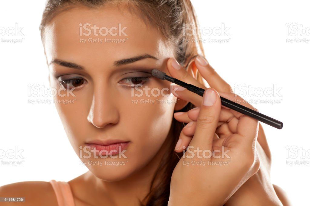 young woman applied eye shadow with applicator stock photo
