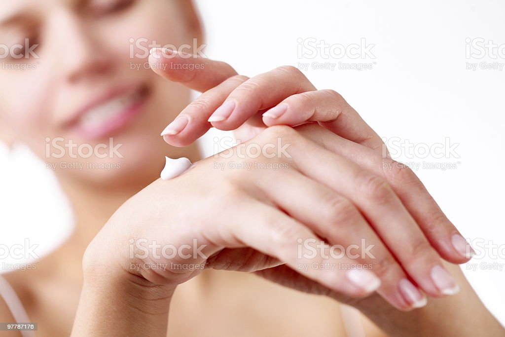 young woman applies cream on her hands stock photo