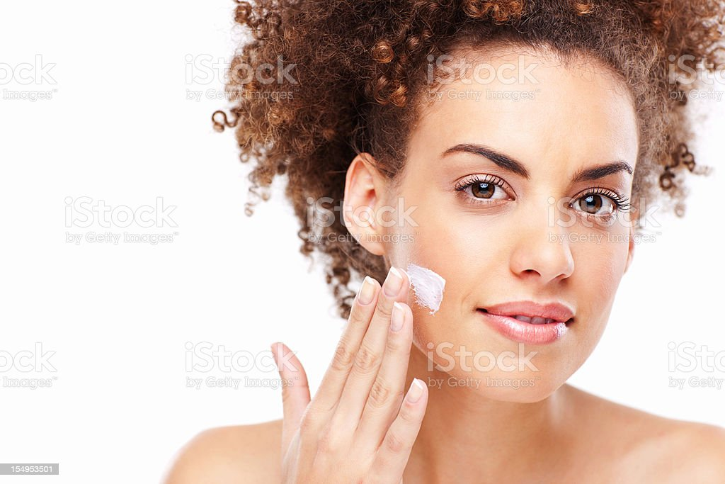 Young Woman Applies Lotion to Her Face royalty-free stock photo