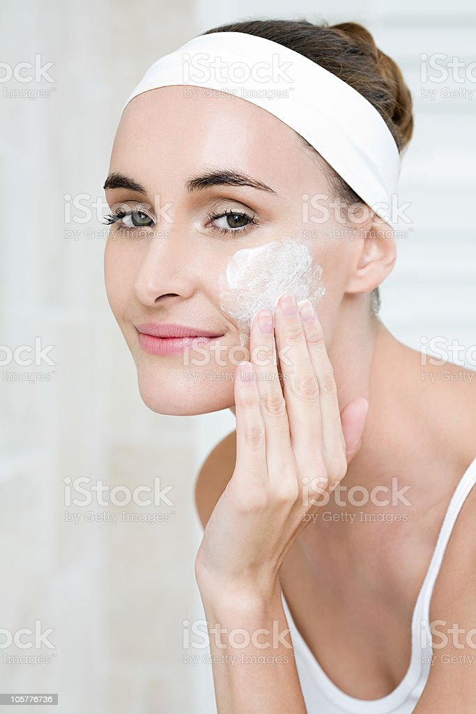 Young woman applying cleanser stock photo