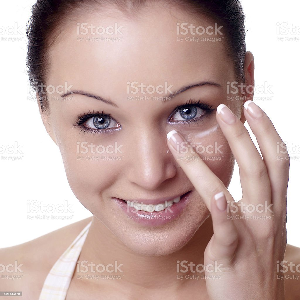 young woman applying creme on face stock photo