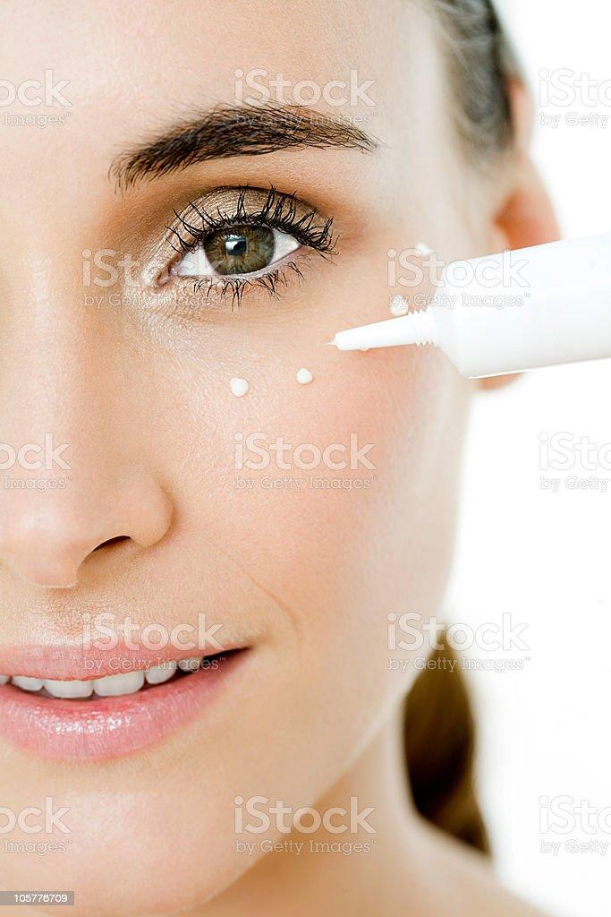 Young woman applying eye cream stock photo