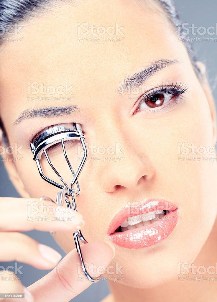 Young woman applying eyelash curler stock photo