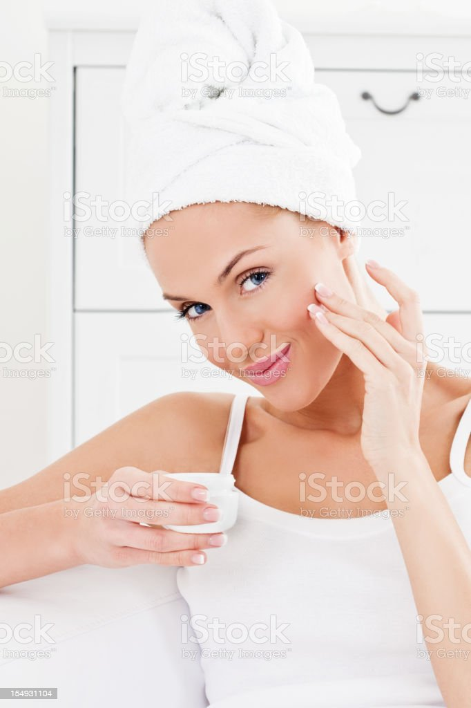 Young woman applying face cream royalty-free stock photo