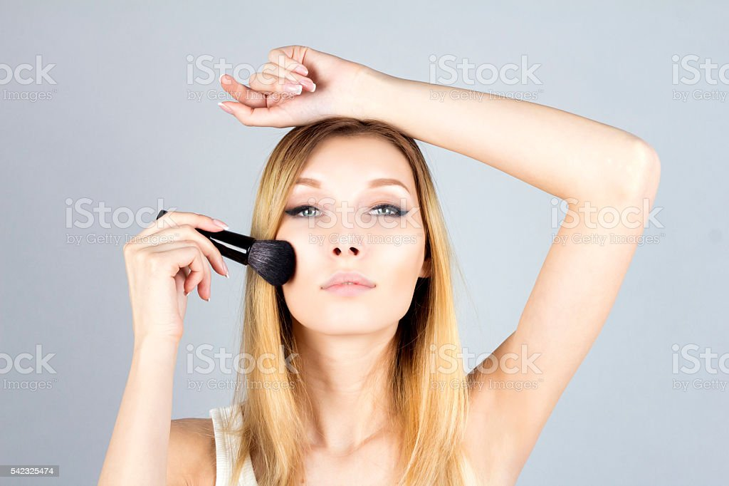Young woman applying foundation with cosmetic brush. Make-up. stock photo