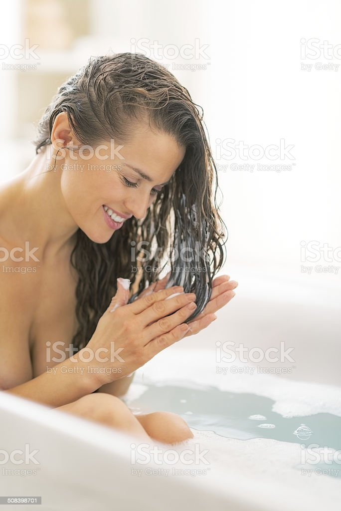 young woman applying hair conditioner in bathtub stock photo