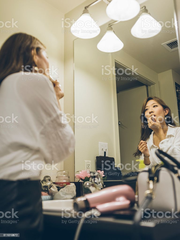 Young woman applying lipstick, looking in mirror stock photo