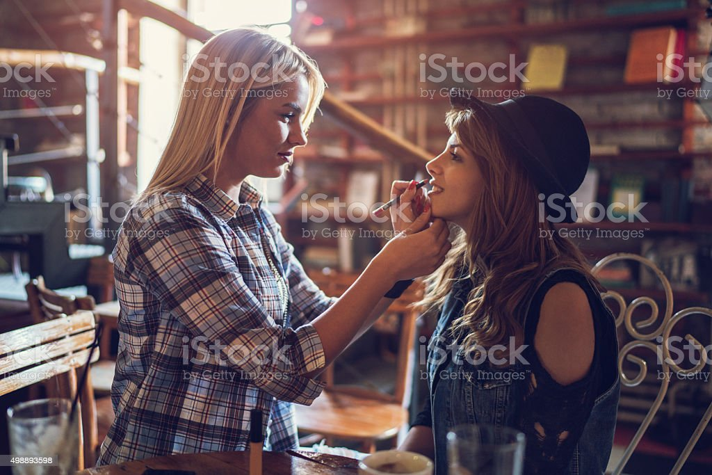 Young woman applying lipstick on her friend's mouth at cafe. stock photo