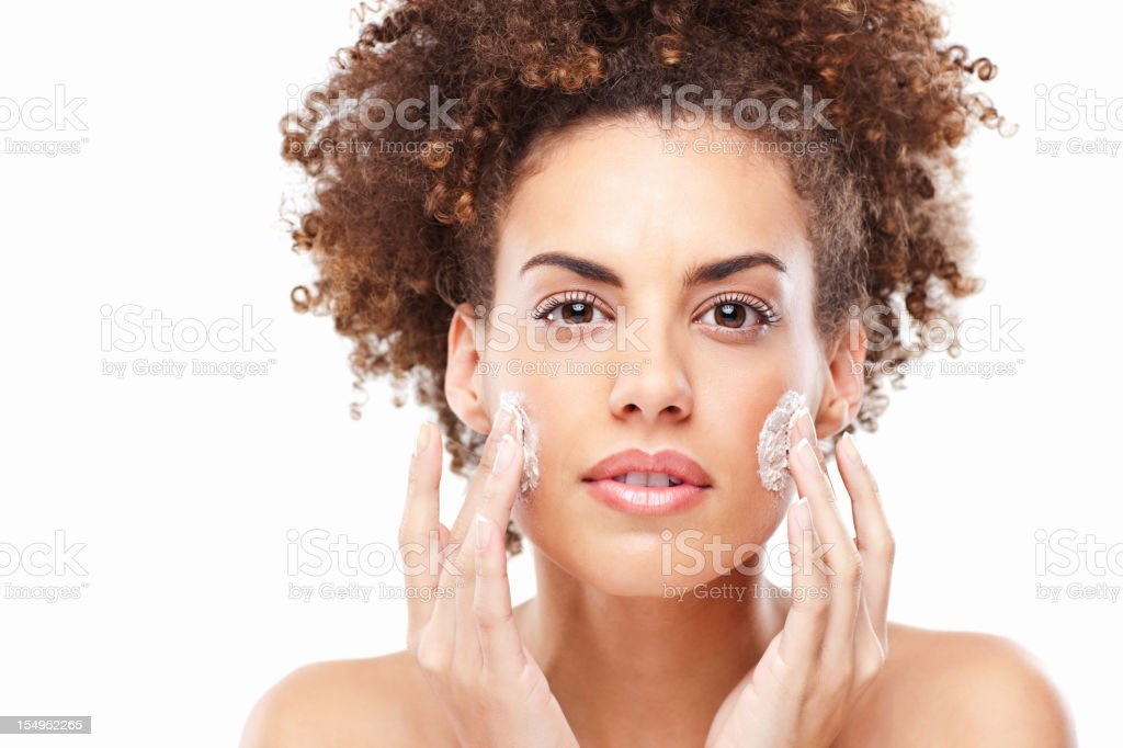 Young Woman Applying Lotion to Her Face royalty-free stock photo