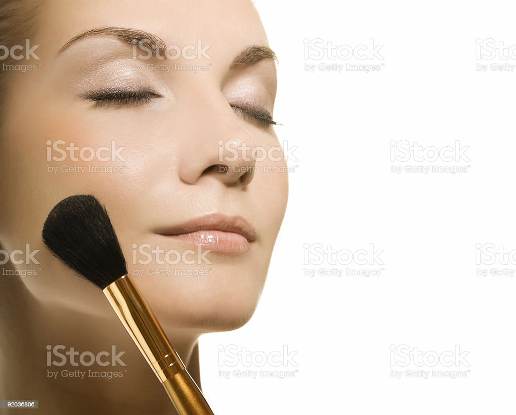 Young woman applying make up on white background royalty-free stock photo