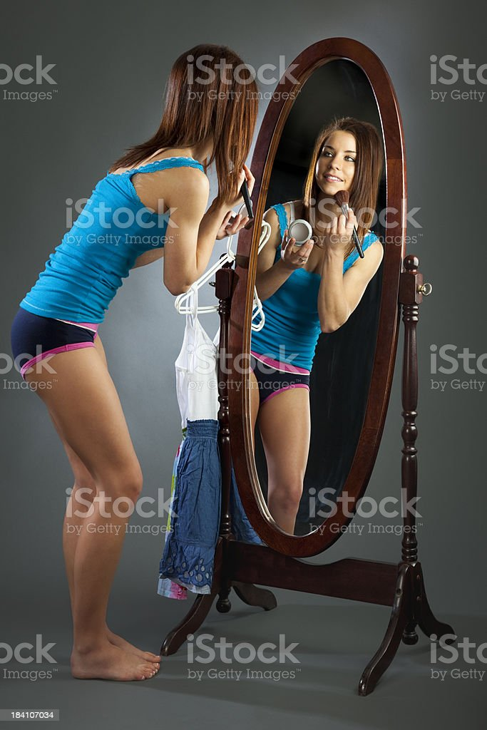 Young Woman Applying Makeup in Mirror stock photo