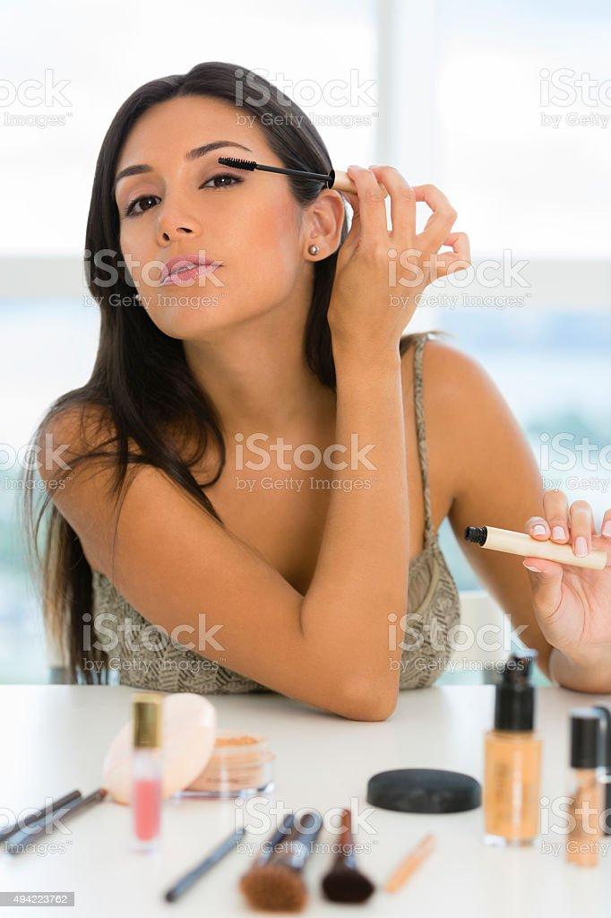 Young woman applying makeup looking at camera stock photo